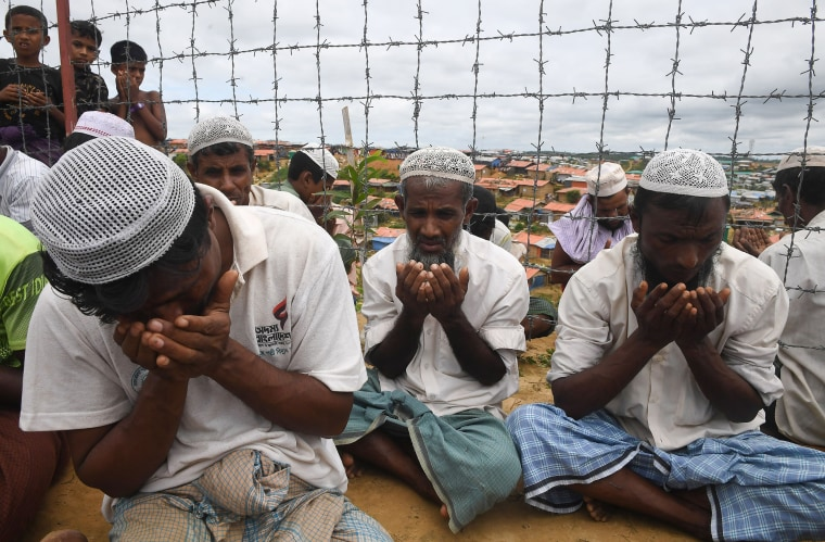 Rohingya refugees perform prayers as they attend a ceremony organised to remember the first anniversary of a military crackdown that prompted a massive exodus of people from Myanmar to Bangladesh