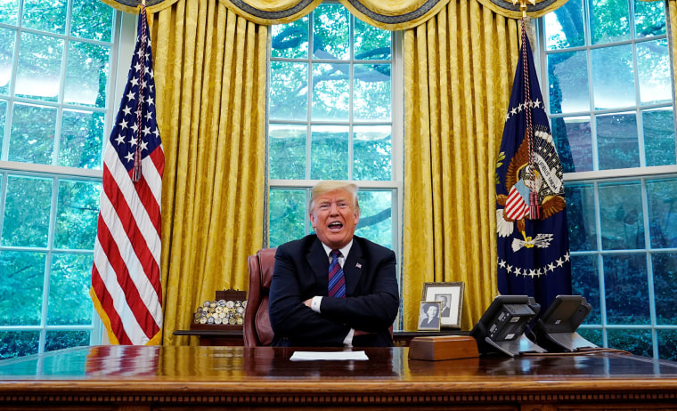 Image:  President Trump sits behind his desk as he makes an announcement on NAFTA in Oval Office in Washington