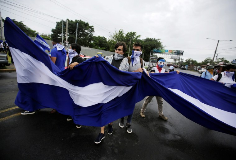 Image: Students hold a national flag while marching during a protest against the government, in Managua