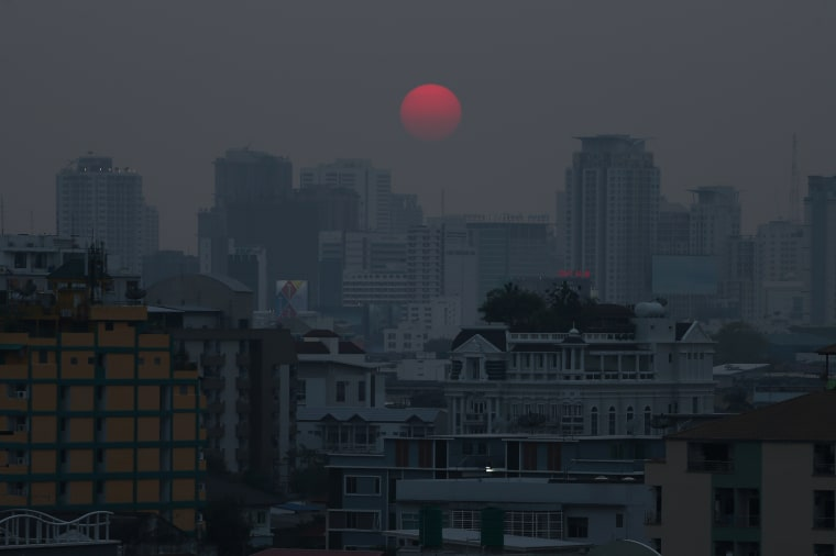 Image: The sun is seen through evening air pollution in Bangkok