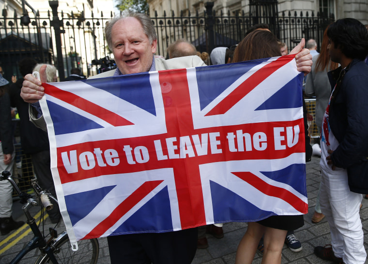 Image: A vote leave supporter holds a Union flag, following the result of the EU referendum, outside Downing Street in London