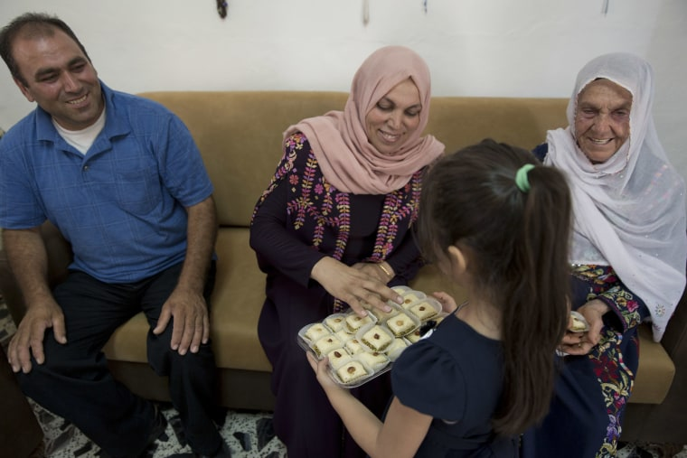 Image: A Palestinian girl offers sweets to family members of Rashida Tlaib