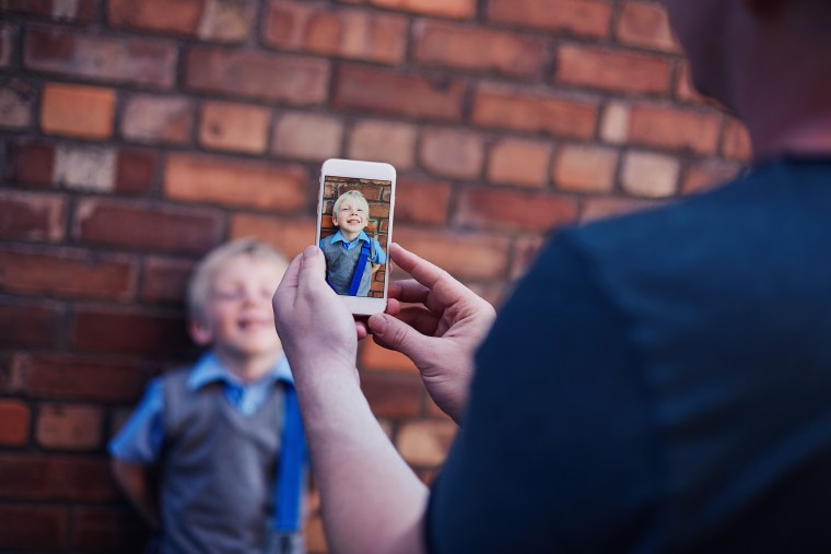Image: A father uses his cell phone to take a photo of his son on his first day school.