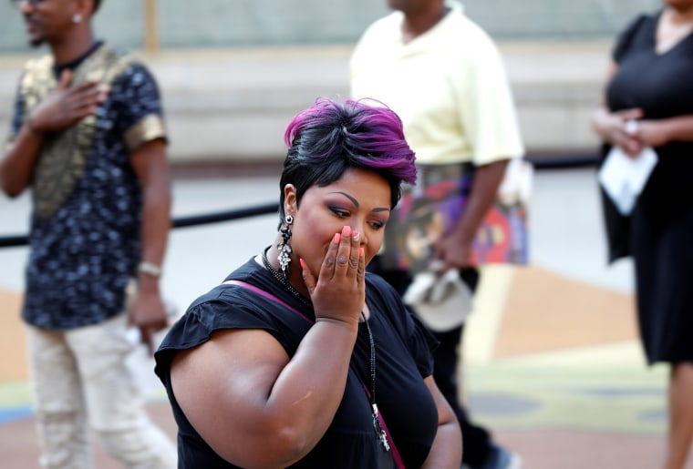 Image: A woman becomes emotional as people file past the body of the late singer Aretha Franklin