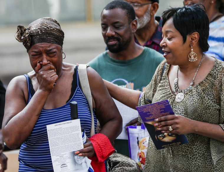 Image: A woman cries as she views the open casket of Aretha Franklin during a public viewing