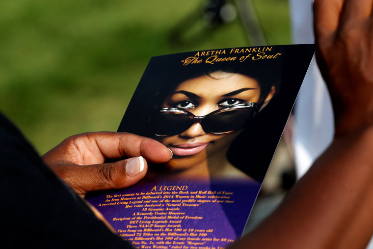 Image: A woman carries a card with an image of Aretha Franklin into the Charles H. Wright Museum of African American History