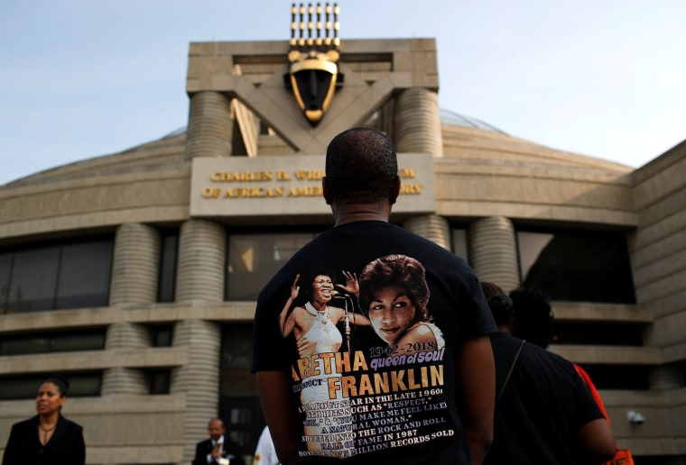 Image: A fan waits outside the Charles H. Wright Museum of African American History