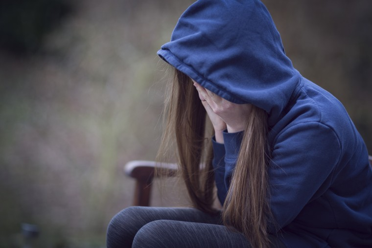 Image: Teenage girl in hooded top, with head in hands in despair