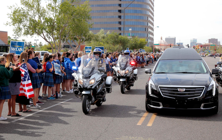 Image: Bystanders look on as a motorcade carrying the casket of Senator John McCain drives from the Arizona State Capitol to a memorial service in Phoenix