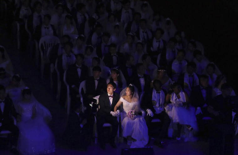Image: A couple watches a screen during a mass wedding at the Cheong Shim Peace World Center