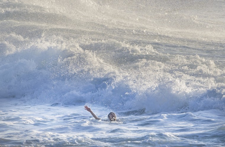 Image: A woman screams for help as she is caught in a rip tide before being rescued