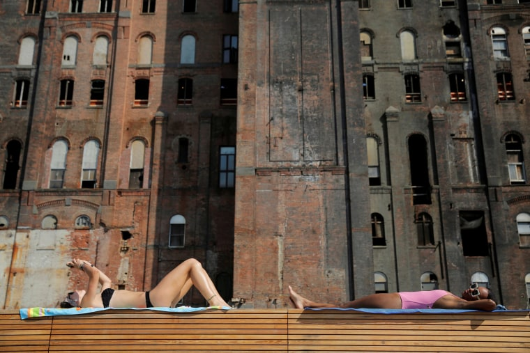 Image: Women lie in the sun in Domino Park as high temperatures hit the region in Brooklyn, New York