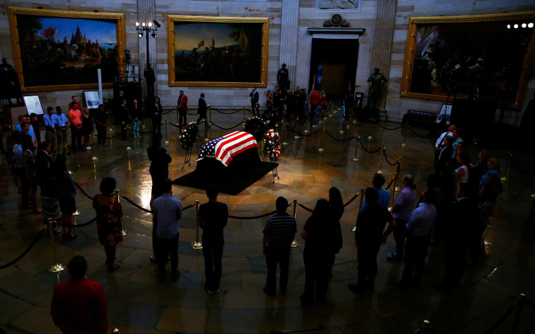 Image: Mourners look at the casket containing the body of late U.S. Senator John McCain as it lies in state inside the U.S. Capitol Rotunda in Washington