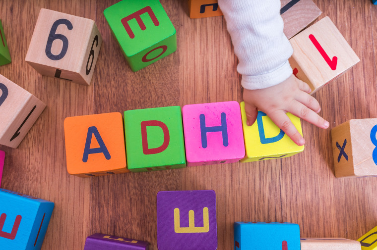 Image: ADHD concept. Baby is playing with cubes with letters.
