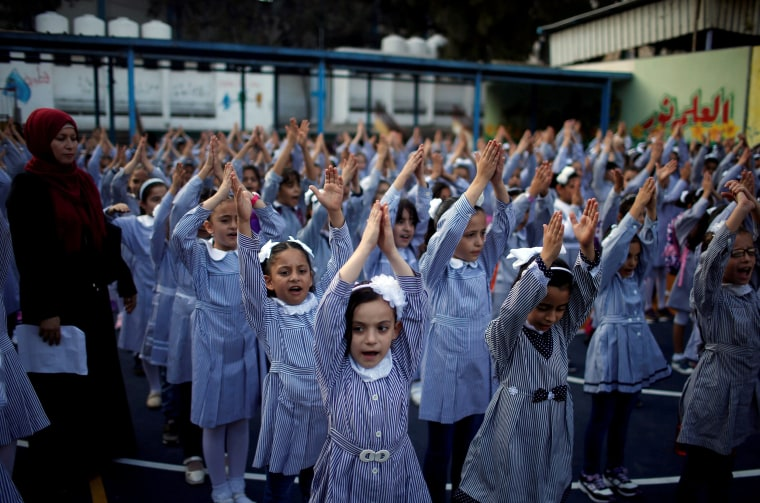 Image: Palestinian schoolgirls participate in the morning exercise at an UNRWA-run school on the first day of a new school year, in Gaza City