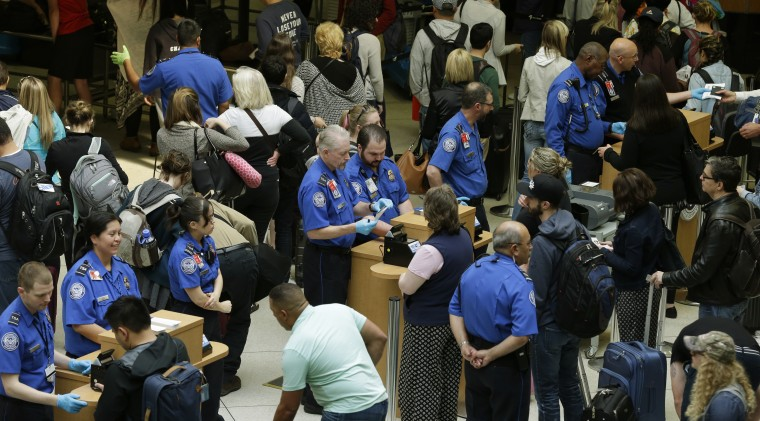 Image: TSA agents check passenger boarding passes and identification at a security screening checkpoint