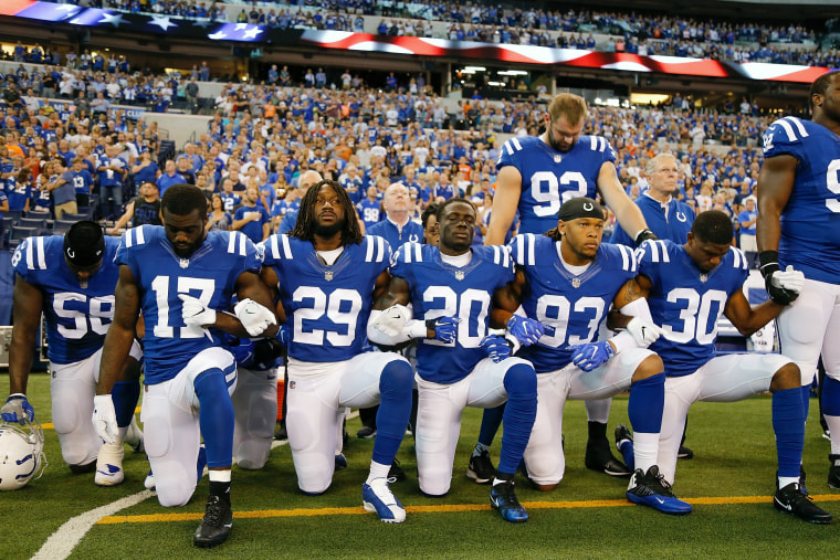 Image: Members of the Indianapolis Colts stand and kneel for the national anthem