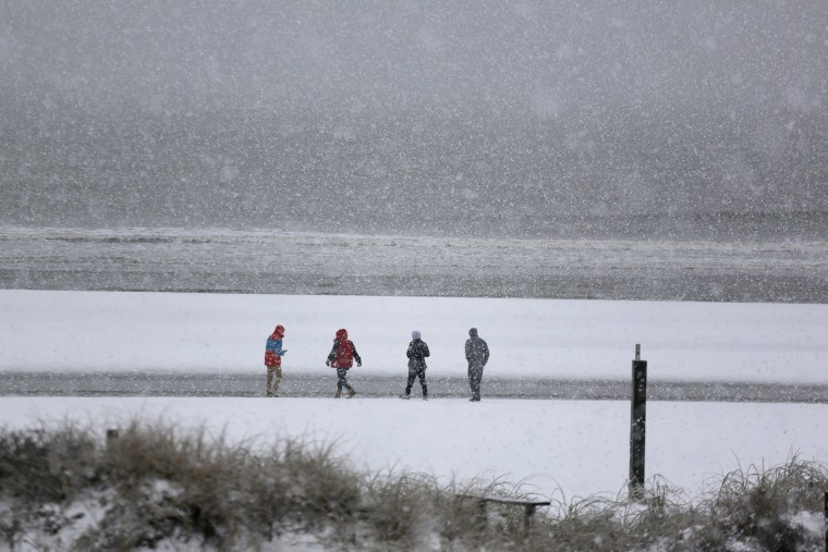 Image: Beach goers make their way down the beach during heavy snowfall on the Isle of Palms