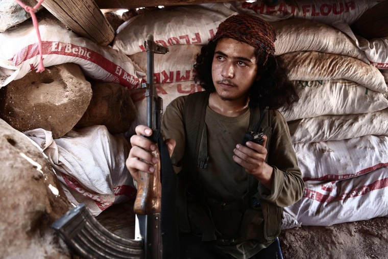 "Image: A Syrian rebel fighter from the recently-formed ""National Liberation Front"" poses with his weapon against a sandbag barricade along the frontline"