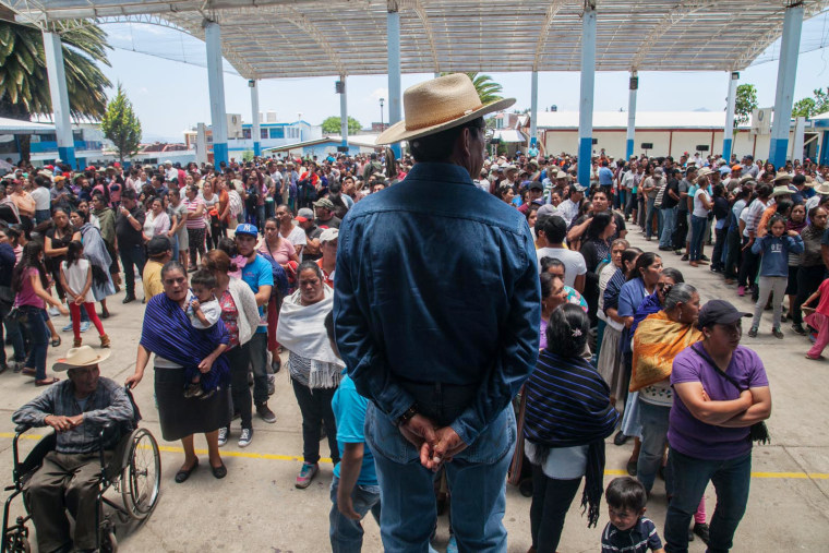Image: Townspeople form behind Salvador Campanur during the community elections on May 27, 2017