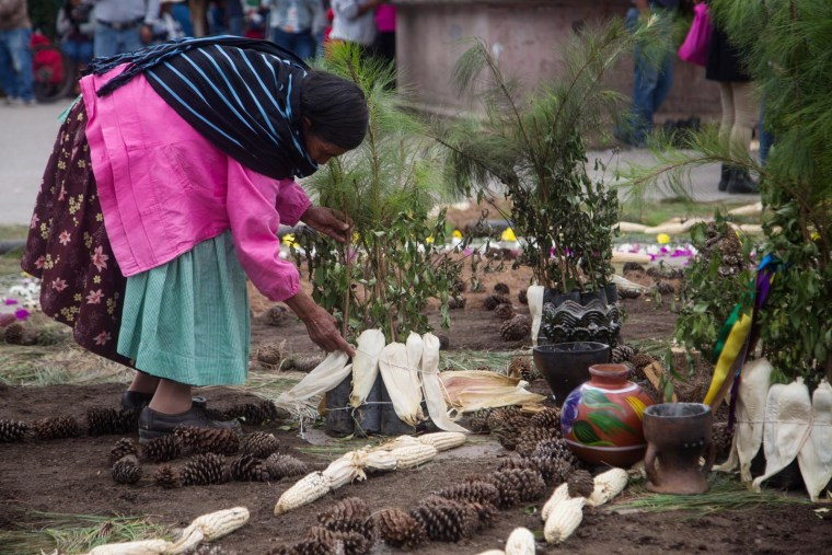 Image: A community member constructs a ceremonial carpet of corn, pine and other sacred items from nature.