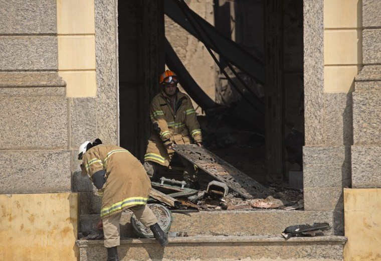 Image: Firefighters remove charred debris from Brazil's National Museum