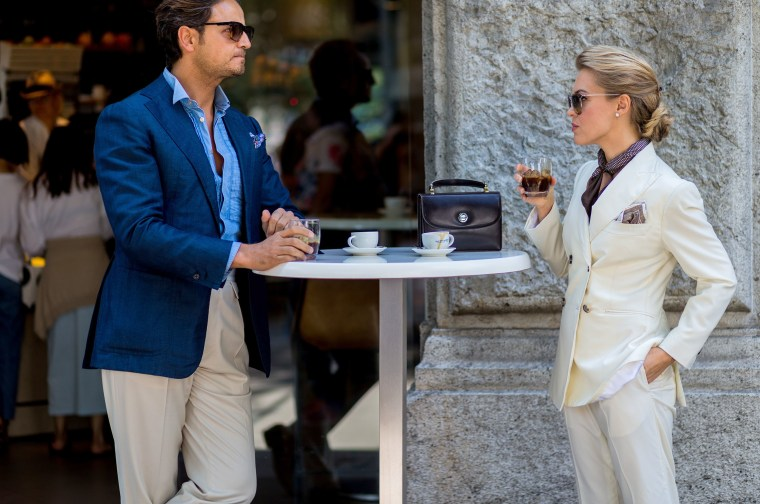 Image: A couple drink Italian coffee outside Jil Sander during the Milan Men's Fashion Week