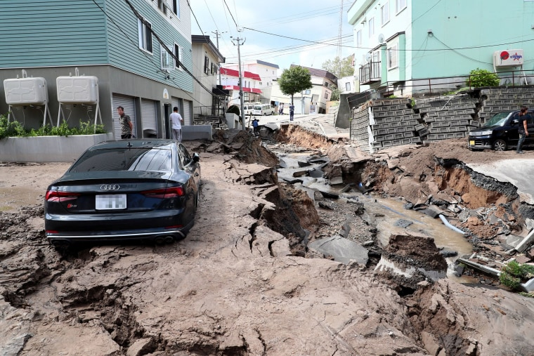 Image: A mud-covered car sits in a destroyed street in Sapporo, Japan