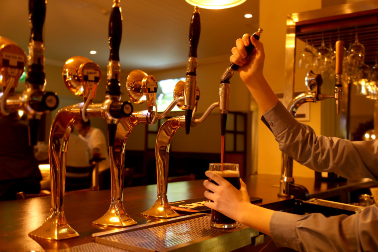 Image: A woman pours a pint of Guinness in a pub in Dublin, Ireland