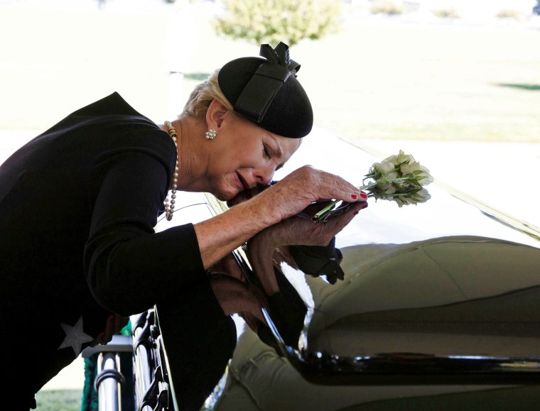 Image: Cindy McCain lays her head on the casket of Sen. McCain during a burial service at the cemetery at the United States Naval Academy in Annapolis