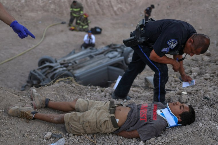 Image: Policeman stands over male who lies injured after crashing vehicle while transporting people who illegally crossed into the U.S. border from Mexico in Penitas, Texas