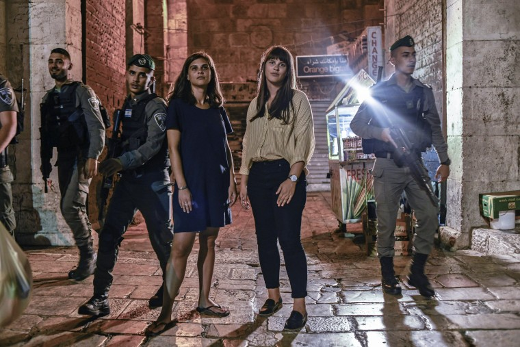 Image: A small unit of Israeli soldiers walks past sisters Clare, left, and Leah Jordan, natives of Kansas City, as they walk through East Jerusalem's Old City.Tanya Habjouqa / for NBC News