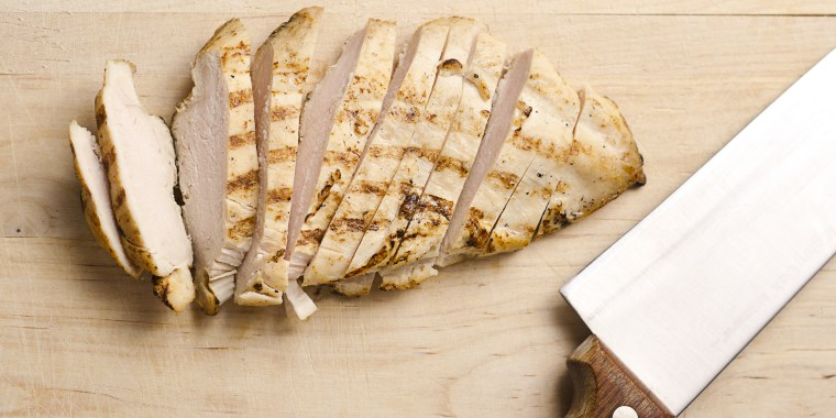 Grilled chicken breast slices on wood