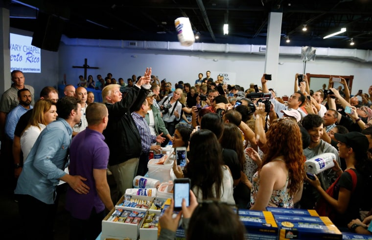 Image: President Trump throws paper towels to residents gathered in a chapel while visiting areas damaged by Hurricane Maria in San Juan, Puerto Rico