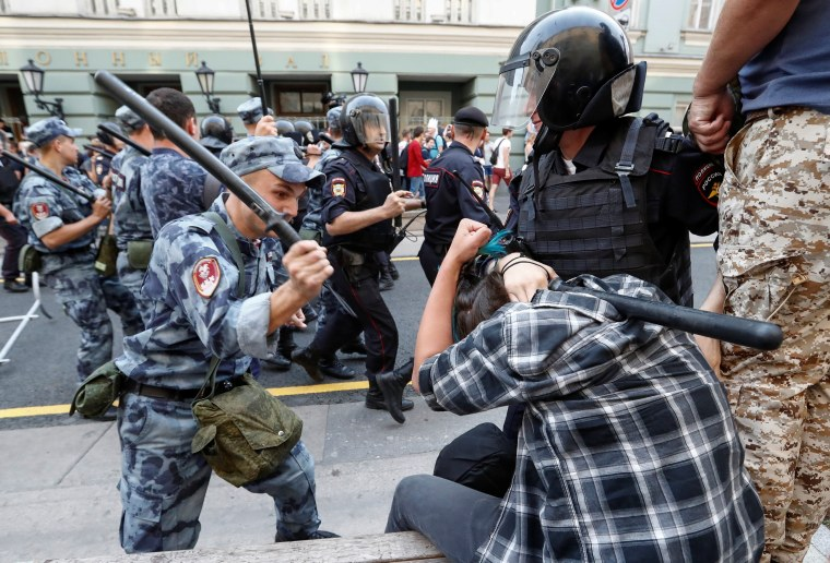 Image: A member of the Russian National Guard beats a protester in Moscow