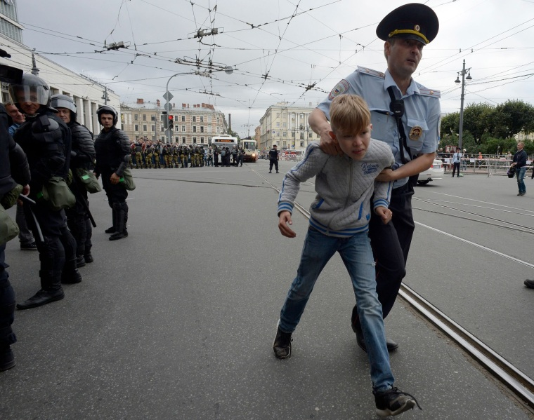 Image: A youth is escorted away from a protest in St. Petersburg, Russia