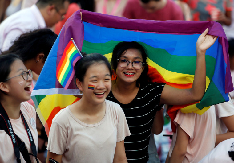 A woman holds a rainbow flag at the Pink Dot event, Singapore's annual gay pride rally, at a park in Singapore
