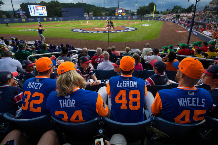 Image: New York Mets players watch a game with little league players