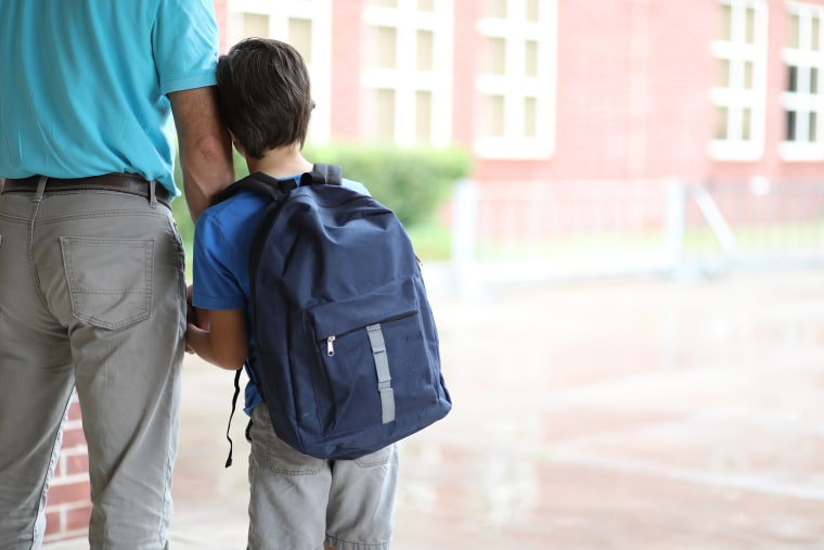 Image: Elementary school boy walks with dad to class