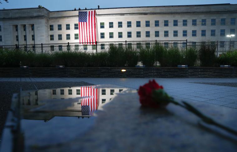Image:  A U.S. flag is unfurled at sunrise at the Pentagon