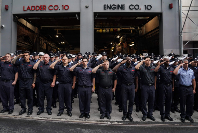 Image: New York City Fire Department  (FDNY) members stand outside Engine 10 and Ladder 10 firehouse for a moment of silence