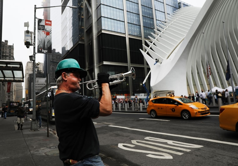 Image: Construction worker Nicky Almer plays Taps across from the World Trade Center site during a morning commemoration ceremony