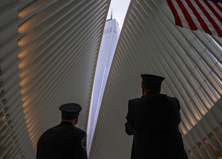 Image: Two members of the New York City fire department look towards One World Trade Center through the open ceiling of the Oculus