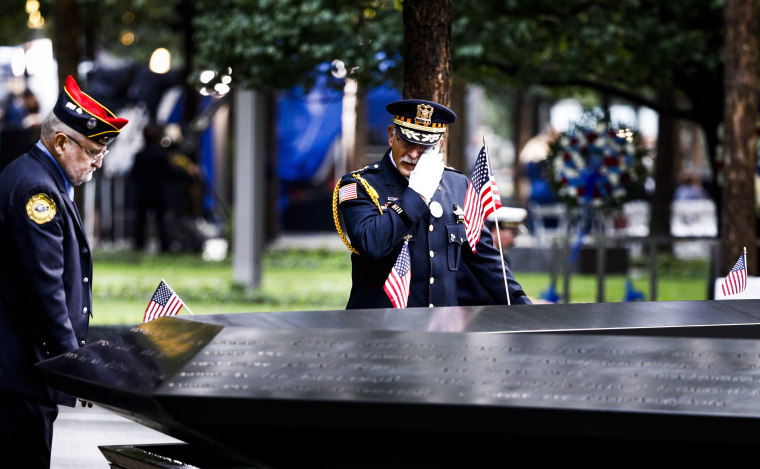 Image: A man wipes a tear while pausing by the South Pool of the 9/11 Memorial