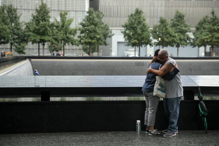 Image: Mourners embrace during a commemoration ceremony for the victims of the September 11 terrorist attacks in New York
