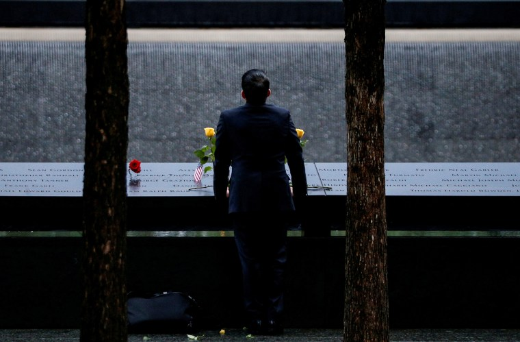 Image: A guest stands among names at the edge of the north reflecting pool at the National 9/11 Memorial and Museum