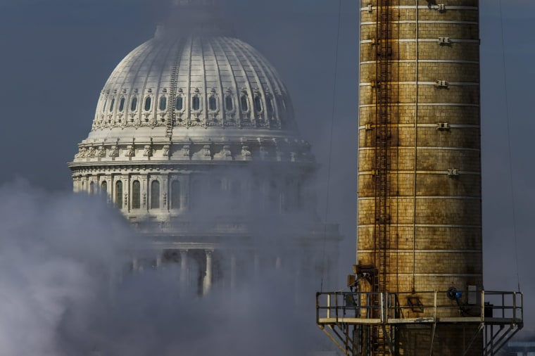 Image: The dome of the U.S. Capitol is seen behind the emissions, and a smokestack, from the Capitol Power Plant