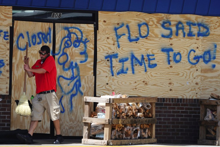 Image: A man sweeps the entrance of a boarded up store before Hurricane Florence comes ashore in Carolina Beach