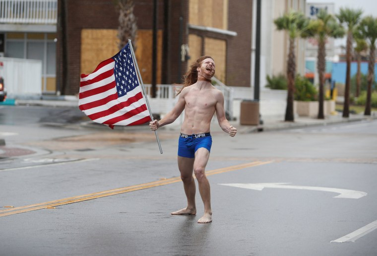 Image: Lane Pittman of Jacksonville, Florida, stands in the wind and rain along Ocean Boulevard during Hurricane Florence in Myrtle Beach