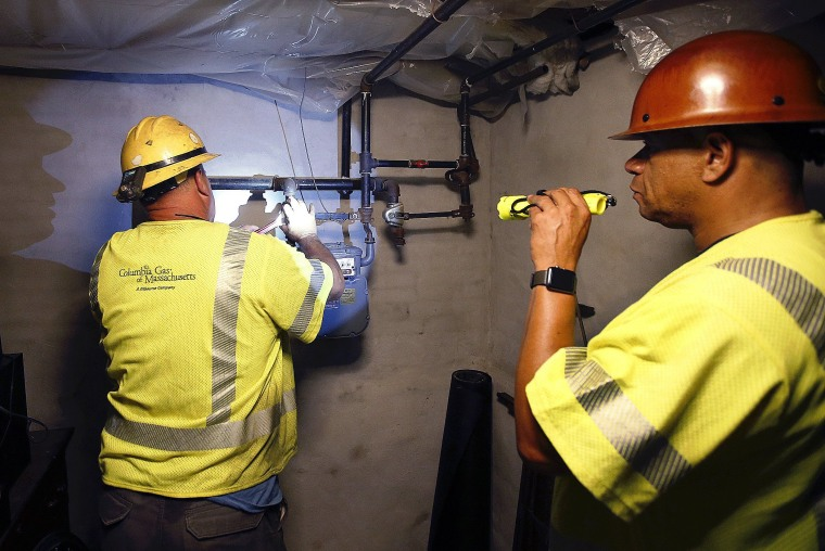 Image: Columbia Gas employee Brian Jones shines a flashlight so his partner, using a wrench, can shut off the gas in a home on Sept. 14, 2018, in Andover, Massachusetts.
